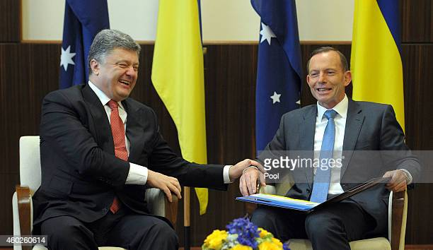 Ukrainian President Petro Poroshenko and Australian Prime Minister Tony Abbott share a joke as they meet at the Federal Government offices on...