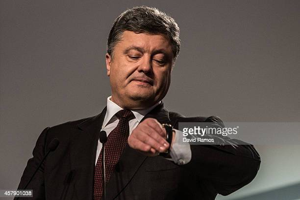 Ukrainian President Petro Poroshenko checks his watch as he speaks to the media on October 26 2014 in Kiev Ukraine Although a low turn out is...