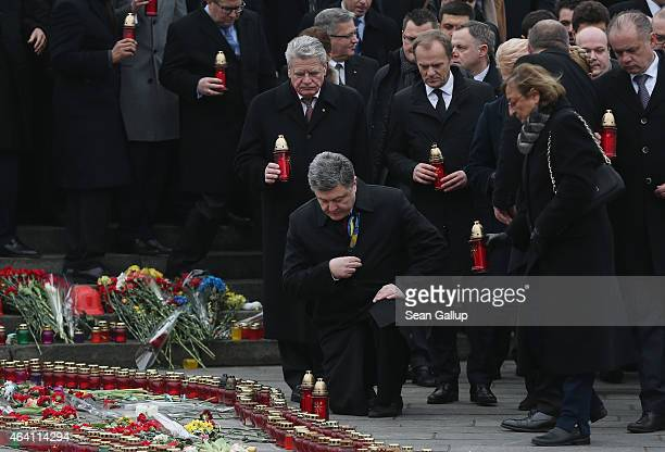 Ukrainian President Petro Poroshenko crosses himself after laying a candle as German President Joachim Gauck and European Council President Donald...