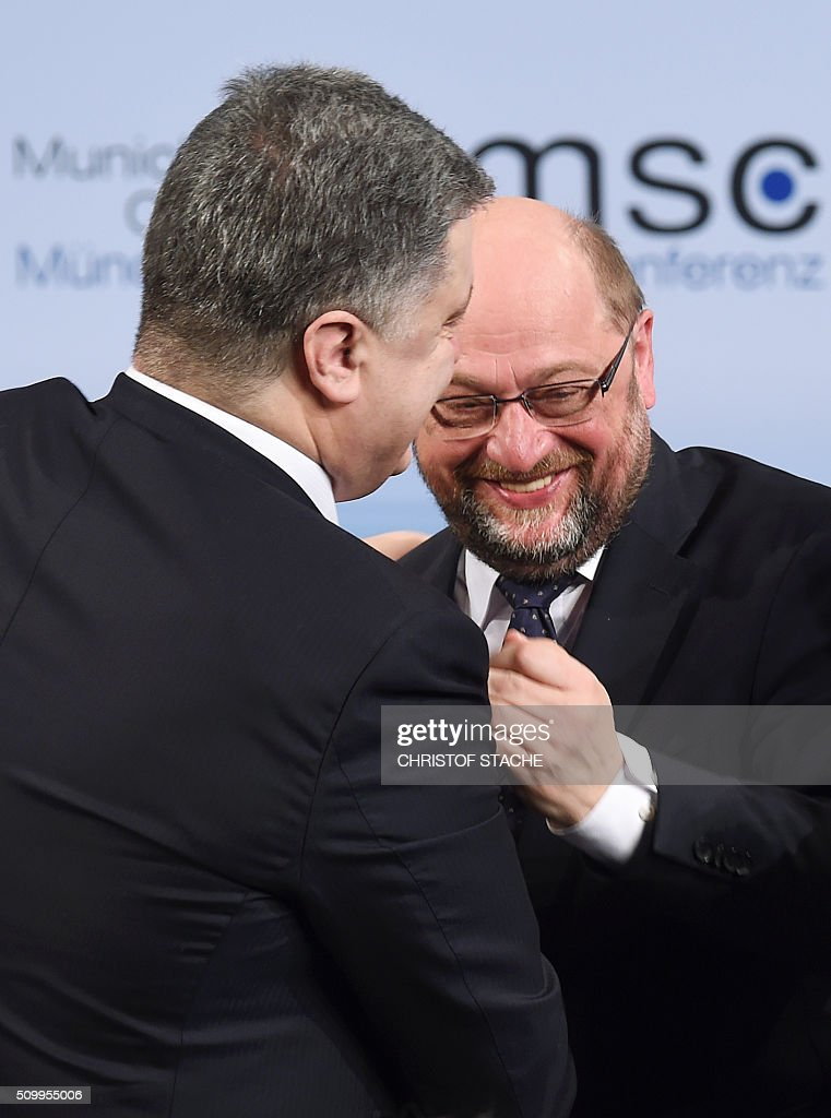 Ukrainian President Petro Poroshenko (L) embraces the President of the European Parliament Martin Schulz (R) during a break at the 52nd Munich Security Conference (MSC) in Munich, southern Germany, on February 13, 2016. / AFP / Christof STACHE