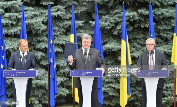 Ukrainian President Petro Poroshenko holds a folder with the ratified agreement on the association of Ukraine and the European Union handed to him by...