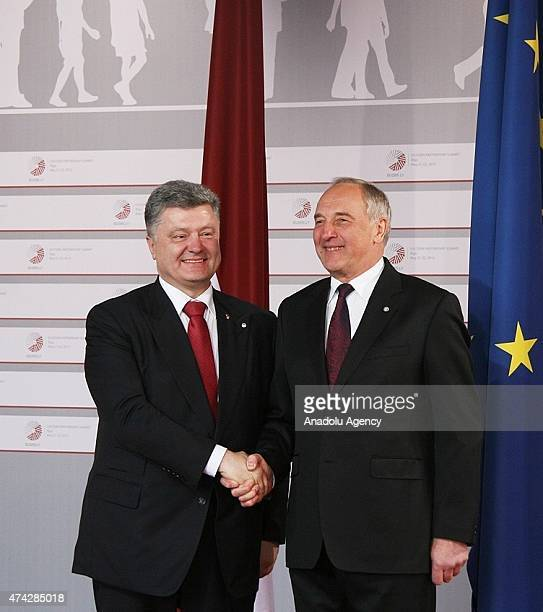 Ukrainian President Petro Poroshenko is welcomed by Latvian President Andris Berzins as he arrives at the House of the Blackhead for a dinner at the...