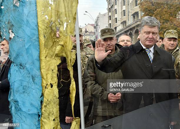 Ukrainian President Petro Poroshenko pays his respect to a Ukrainian flag found in a war zone in the eastern part of the country close to remains of...