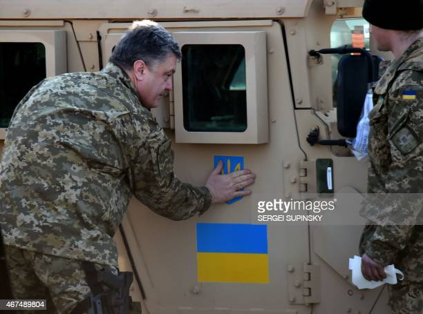 Ukrainian President Petro Poroshenko sticks an Ukrainian flag and the state emblem on an armoured vehicle at Kiev airport on March 25 2015 during a...