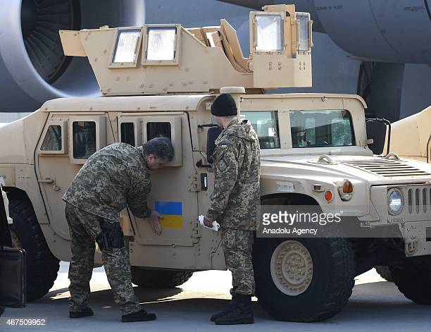 Ukrainian President Petro Poroshenko sticks an Ukrainian flag on an armored vehicle at Boryspil airport in Kiev on March 25 2015 during a welcoming...
