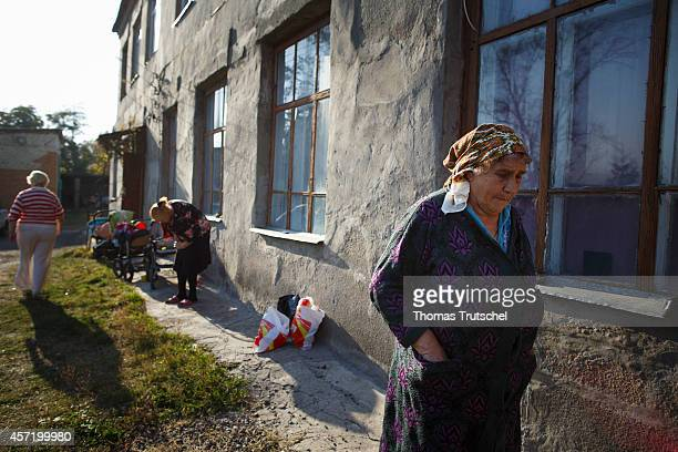 Ukrainian refugees stand outside refugee accommodations in on October 14 2014 in Kharkiv Ukraine German Development Minister Gerd Mueller is on a...