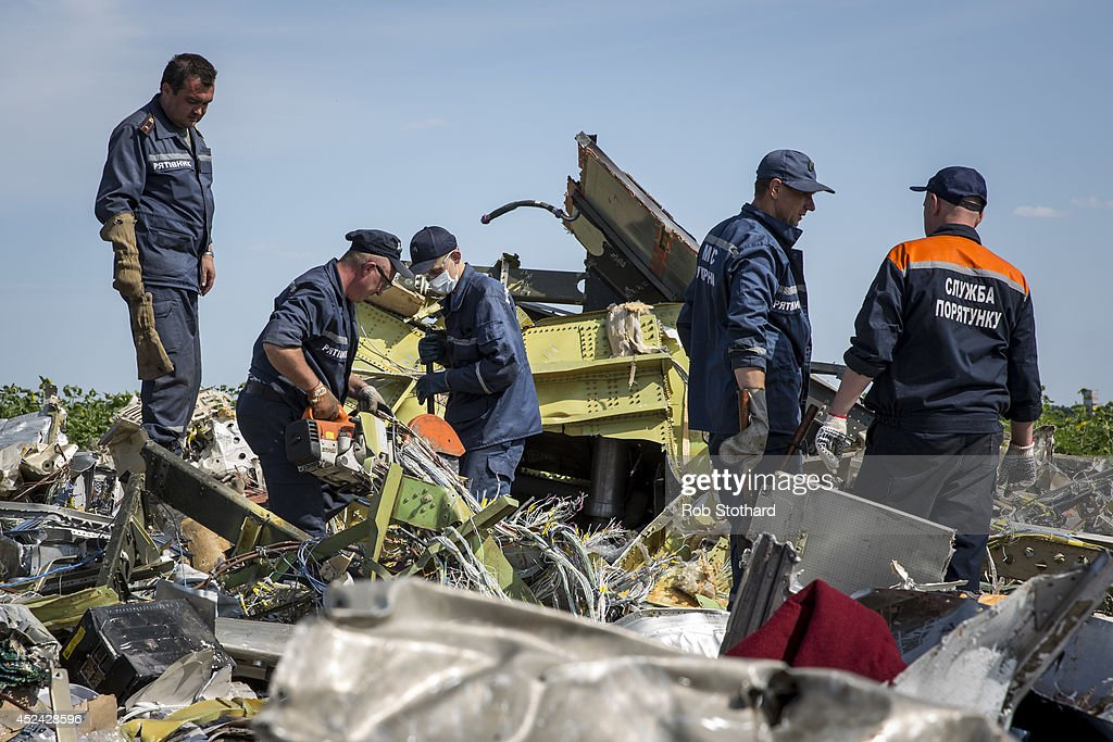 Ukrainian rescue servicemen inspect part of the wreckage of Malaysia Airlines flight MH17 on July 20, 2014 in Rassipnoye, Ukraine. Malaysia Airlines flight MH17 was travelling from Amsterdam to Kuala Lumpur when it crashed killing all 298 on board including 80 children. The aircraft was allegedly shot down by a missile and investigations continue over the perpetrators of the attack.