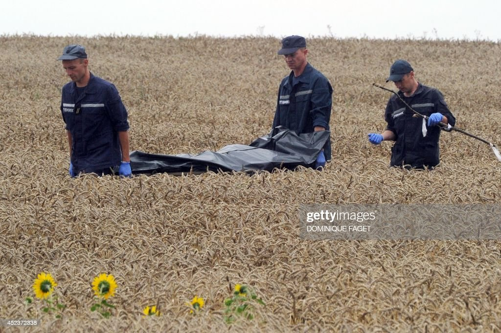 Ukrainian rescue workers carry the body of a victim on a stretcher through a wheat field at the site of the crash of a Malaysia Airlines plane carrying 298 people from Amsterdam to Kuala Lumpur in Grabove, in rebel-held east Ukraine, on July 19, 2014. Ukraine and pro-Russian insurgents agreed on July 19 to set up a security zone around the crash site of a Malaysian jet whose downing in the rebel-held east has drawn global condemnation of the Kremlin. Outraged world leaders have demanded Russia's immediate cooperation in a prompt and independent probe into the shooting down on July 17 of flight MH17 with 298 people on board.