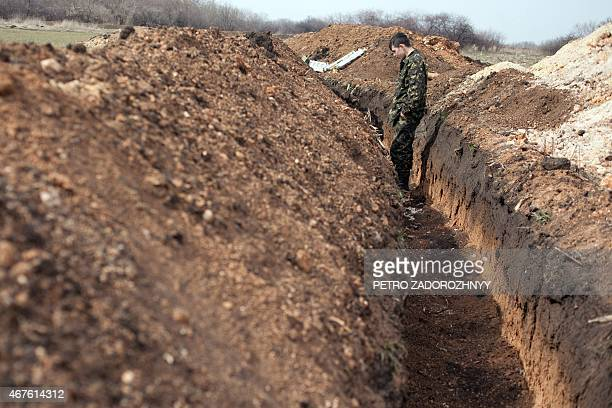 Ukrainian serviceman attends in a trench on the position of Ukrainian forces not far from Lysychansk Lugansk region on March 26 2015 The United...