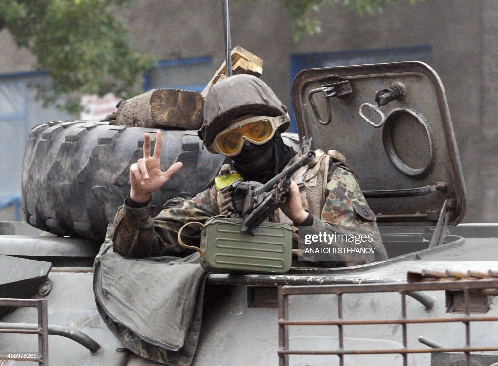 A Ukrainian serviceman gestures as he patrols on September 23 2014 on armored personnel carrier in a suburb of the eastern town Debaltseve in the...