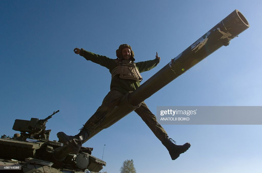 A Ukrainian serviceman gestures as he sits on a tank barrel in a basecamp near the town of Debaltseve in the Donetsk region on October 6 2014 The...