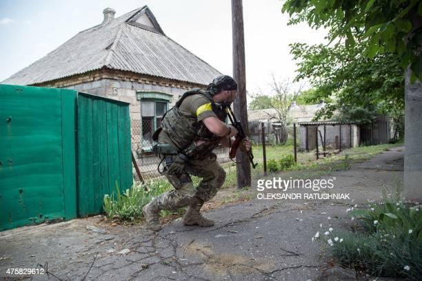 A Ukrainian serviceman holds gun during fightings in the Ukrainian city of Mariinka in the region of Donetsk on June 4 2015 Ukrainian President...