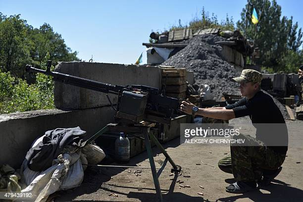 A Ukrainian serviceman kneels at a post with a heavy machine gun at a position held by Ukrainian forces near the village of Dzerzhynsk Donetsk region...
