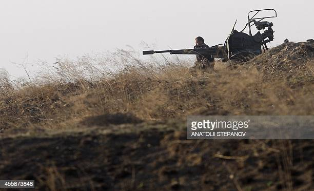 A Ukrainian serviceman mans a position next to an antiaircraft machinegun on September 21 2014 near the town of Debaltseve in the region of Donetsk...