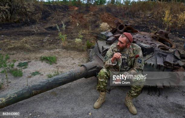 Ukrainian serviceman sits on the turret of a tank to be used for a monument on September 06 2017 in Avdiivka Ukraine The frontlinecity Avdiivka is...