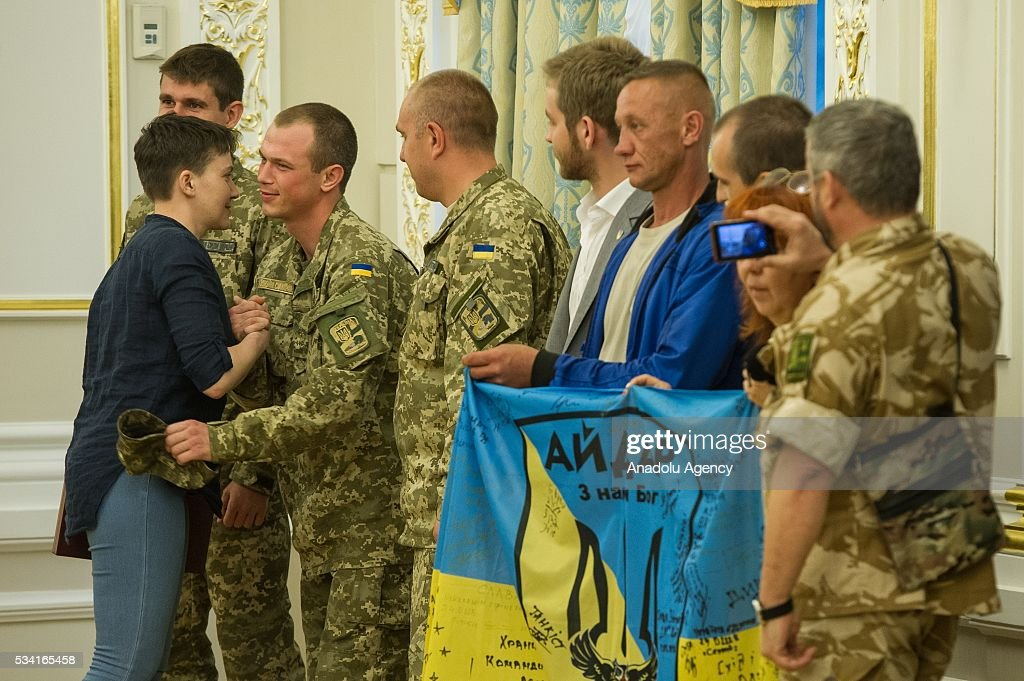 Ukrainian servicemen congratulate Nadiya Savchenko (left) during joint press conference of Ukrainian President Petro Poroshenko and released Ukrainian pilot Nadiya Savchenko in the President's Administration in Kiev, Ukraine, May 25, 2016.