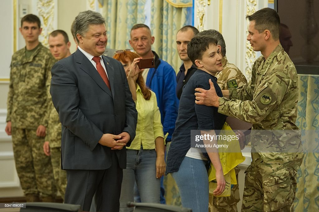 Ukrainian servicemen congratulate Nadiya Savchenko (right) during joint press conference of Ukrainian President Petro Poroshenko and released Ukrainian pilot Nadiya Savchenko in the President's Administration in Kiev, Ukraine, May 25, 2016.