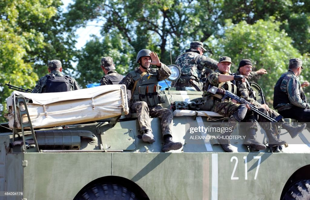 Ukrainian servicemen of volunteer battalion Azov ride on their APC towards the small Ukrainian city of Novoazovsk, in the Donetsk region on August 26, 2014. Clashes erupted on August 26 close to the Russian border in the south of the war-torn Donetsk region where Ukraine accuses Moscow of trying to open a 'new front' into government-held territory. AFP journalists saw thick smoke rising near Novoazovsk, about 12 kilometres from the Russian border, as fleeing residents said mortar strikes hit the coastal town.
