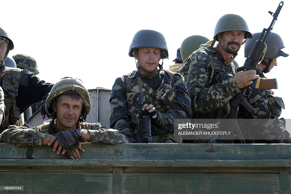 Ukrainian servicemen ride on a military vehicle towards the small Ukrainian city of Novoazovsk, in the Donetsk region on August 26, 2014. Clashes erupted on August 26 close to the Russian border in the south of the war-torn Donetsk region where Ukraine accuses Moscow of trying to open a 'new front' into government-held territory. AFP journalists saw thick smoke rising near Novoazovsk, about 12 kilometres from the Russian border, as fleeing residents said mortar strikes hit the coastal town.