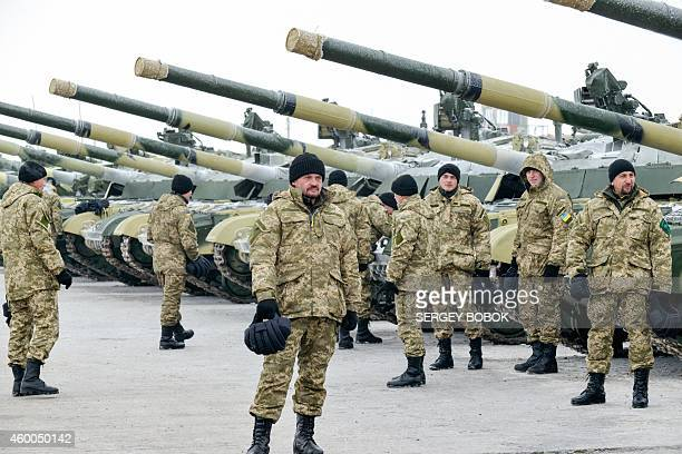 Ukrainian servicemen stand near tanks after a ceremony with the Ukrainain president for the delivery of more than 100 pieces military equipment...