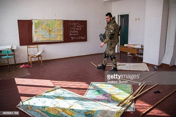 Ukrainian soldier from the Azov Battalion walks past maps of Europe inside a school that has been converted into temporary barracks for soldiers...