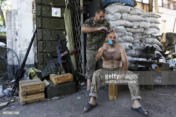 A Ukrainian soldier get a trim from another at a posititon held by Ukrainian forces at the destroyed Butovka mine near Donetsk airport on July 30...