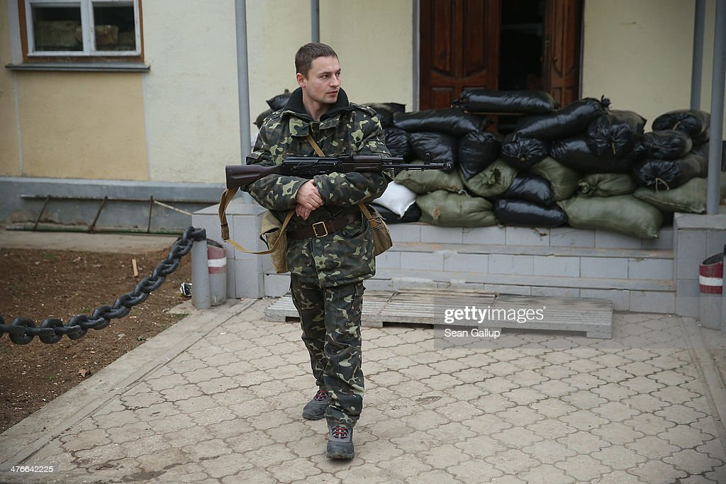 A Ukrainian soldier inside the Belbek military base cradles a Kalashnikov machine gun next to barracks and sandbags in the early morning following a tense night on March 4, 2014 in Lubimovka, Ukraine. Tensions at the base, where between 300 and 400 Ukrainian soldiers are stationed, were high overnight as a 4pm deadline the day before reportedly given by Russian troops for the Ukrainians to surrender passed and the troops feared the Russians might attack the base overnight. Many of the soldiers have family that live in apartment blocks just outside the base and about two dozen family members braved the cold ready and huddled with tea and cognac by a campfire outside, ready to block the road to the base entrance should the Russians appear.
