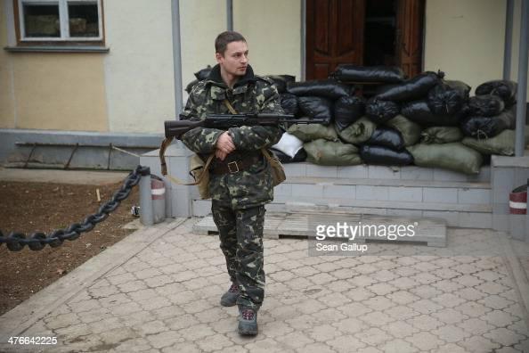 Ukrainian soldier inside the Belbek military base cradles a Kalashnikov machine gun next to barracks and sandbags in the early morning following a...