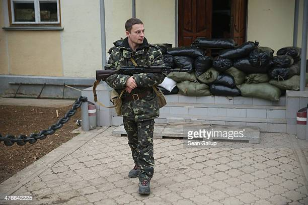 Ukrainian soldier inside the Belbek military base cradles a Kalashnikov machine gun next to barracks and sandbags in the early morning following a...