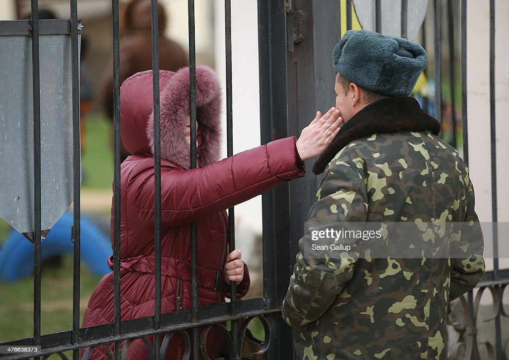 A Ukrainian soldier inside the Belbek military base gets an affectionate pet from a woman who was among approximately two dozen who spent the night outside the gate in support of the men on March 4, 2014 in Lubimovka, Ukraine. Tensions at the base, where between 300 and 400 Ukrainian soldiers are stationed, were high overnight as a 4pm deadline the day before reportedly given by Russian troops for the Ukrainians to surrender passed and the troops feared the Russians might attack the base overnight. Many of the soldiers have family that live in apartment blocks just outside the base and about two dozen family members braved the cold ready to block the road to the base entrance should the Russians appear.