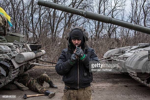 Ukrainian soldier lights a cigarette while his unit's tank is repaired on a roadside leading out of Debaltseve on February 19 2015 in Artemivsk...