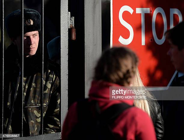 A Ukrainian soldier looks out through a gate near a 'stop' sign as Ukrainian soldiers wait inside the Sevastopol tactical military brigade base near...