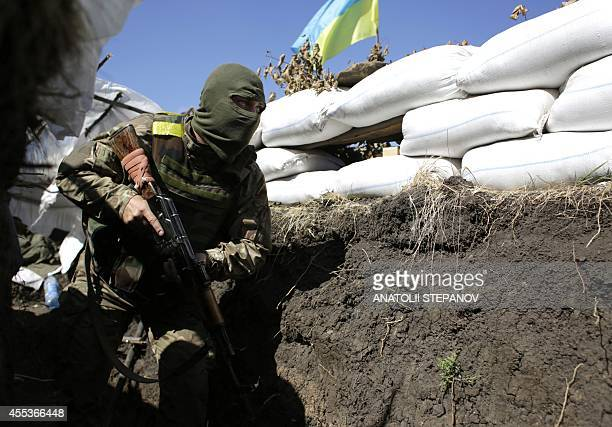A Ukrainian soldier moves along a trench at their position close to the small eastern Ukrainian city of Pervomaysk in Lugansk region on September 13...