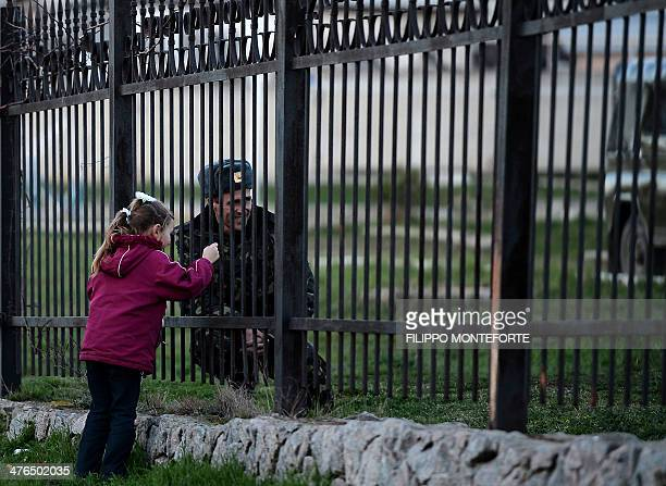 A Ukrainian soldier speaks to his daughter through a gate as he waits inside the Sevastopol tactical military brigade base near Belbek in Sevastopol...