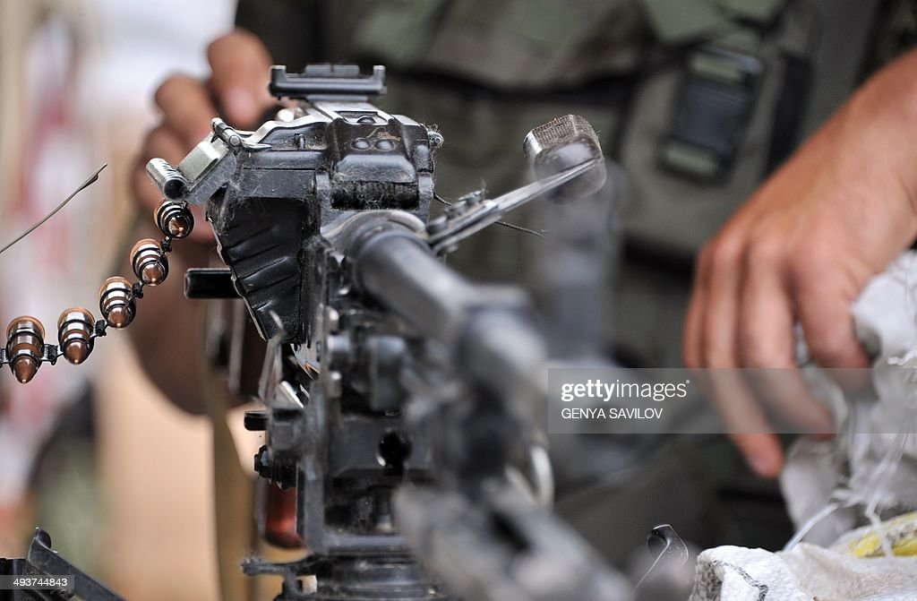A Ukrainian soldier stands behind a machinegun at a checkpoint on the road between Izyum to Slavyansk on May 25 2014 Ukraine began voting on Sunday...