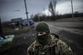 A Ukrainian soldier stands watch on a road between Debaltseve and the Ukrainiancontrolled town of Artemivsk in the Donetsk region on February 2 2015...