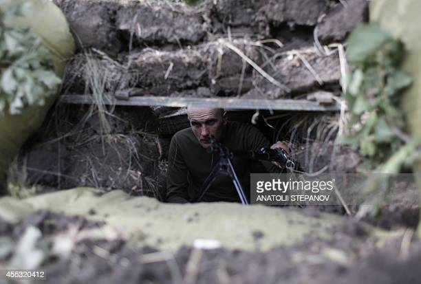 A Ukrainian soldier takes position in a trench near the eastern Ukrainian city of Popasna in the Lugansk region on September 12 2014 The United...