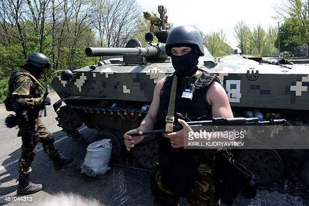 A Ukrainian soldier wearing a helmet and a balaclava stands guard by an Amoured Personnel Carriers at a road checkpoint about 25 km from the eastern...