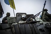 Ukrainian soldiers are seen in an armoured vehicle topped with a Ukrainian flag near the city of Artemivsk in the Donetsk region before heading to...