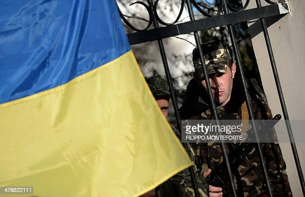 Ukrainian soldiers look out through a gate from behind a Ukrainian flag as they wait inside the Sevastopol tactical military brigade base near Belbek...