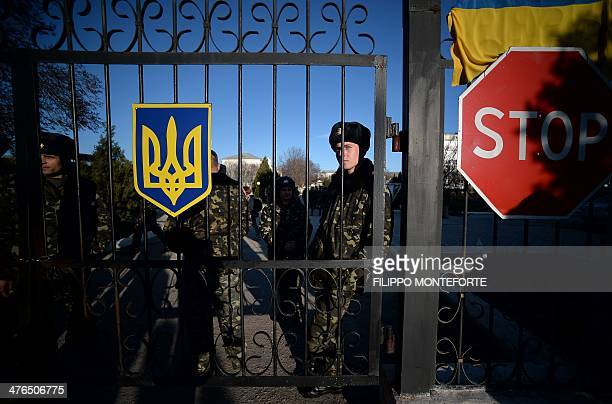 Ukrainian soldiers look out through a gate near a 'stop' sign as they wait inside the Sevastopol tactical military brigade base near Belbek in...