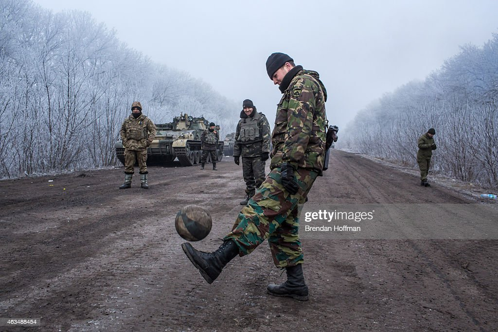 Ukrainian soldiers play football on the road leading to the embattled town of Debaltseve on February 15, 2015 outside Artemivsk, Ukraine. A ceasefire scheduled to go into effect at midnight was reportedly observed along most of the front, save for near the embattled town of Debaltseve.