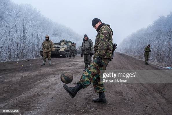 Ukrainian soldiers play football on the road leading to the embattled town of Debaltseve on February 15 2015 outside Artemivsk Ukraine A ceasefire...