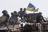Ukrainian soldiers sit atop an armoured personnel carrier during patrol in the Donetsk region on September 3 2014 Beleaguered Ukrainian President...