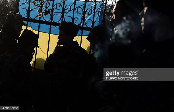 Ukrainian soldiers smoke cigarettes as they wait inside the Sevastopol tactical military brigade base in Sevastopol on March 3 2014 Russian forces...