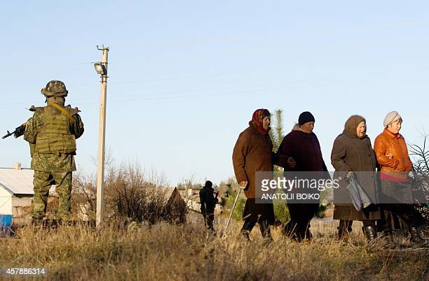 Ukrainian soldiers stand guard as women walk by on their way to a polling station in the village of Raygorodka near Lugansk on October 26 during...