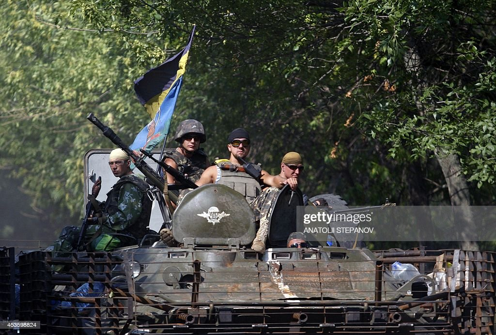 Ukrainian soldiers stand in their APC as it enters the small eastern Ukrainian city of Vuglegirsk Donetsk region on August 14 freed by the country's...