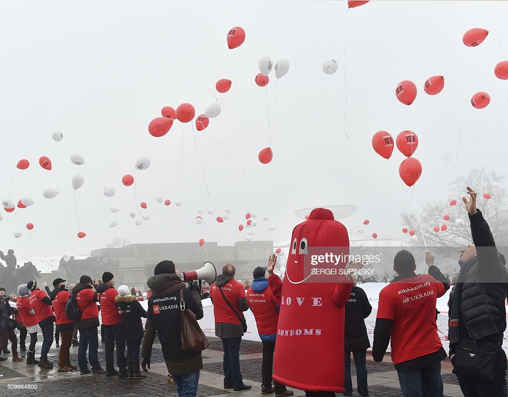 Ukrainian students and a man dressed in a Condom release balloons during their action at WWII open air museum in Kiev on February 13, 2016 to mark the International Condom Day. International Condom Day seeks to promote the use of condoms as a means of preventing unwanted pregnancies and sexually transmitted infections (STI's). It is an informal observance celebrated in conjunction with Valentine's Day. The holiday is also promoted by the AHF (AIDS Healthcare Foundation) in an effort to reduce the spread of HIV thru safe sex practices. / AFP / SERGEI SUPINSKY