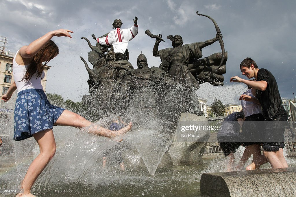 Ukrainian students play around in a fountain as they celebrate the end of their school term at Independence Square downtown Kiev, Ukraine, May 27, 2016.