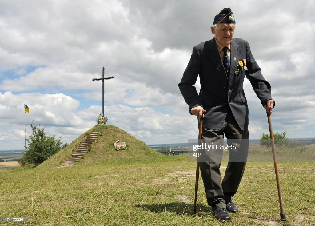 A Ukrainian veteran of the 'Galician' SS Division, walks past a memorial on July 21, 2013, near the village of Pidhirci, some 70km west of Lviv. The 'Galician' SS Division or 14th Grenadier Division of the Waffen SS 'Galician' was a World War II German military formation formed in 1943 (initially called the 14th SS-Volunteer Division 'Galician') of volunteers from Galicia, western Ukraine, which later also incorporated Slovack, Czech and Dutch volunteers.